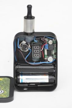 Inside Buzzbox Mod PV E-Cigarette    Two 18650 Li-ion batteries, Variable volt step-down regulator, voltmeter, 50g tin, rebuildable atomizer.