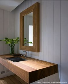 Floating vanity with a cut in skin, love that the sink edges don't run over the wood surface.