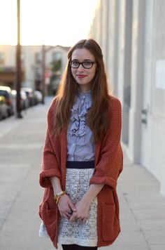 this is look is just great. ruffle blouse, lace skirt contrasted with an oversized orange sweater.