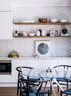 herringbone subway tile pattern backsplash, open shelving in wood, black wishbone chairs - super modern kitchen design