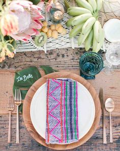An Island-Inspired, Backyard Wedding Anniversary Dinner | Martha Stewart Weddings - Monstera leaves calligraphed with guests' names were tucked under wooden chargers flanked by copper flatware from Borrowed Blu. Colorful, woven textiles graced each white plate, and blue and clear goblets were provided for toasting.