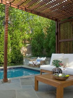 A pergola-covered slate patio is furnished with wood and white cushioned furniture, including a poolside sitting area with an ottoman. Trees surrounding the space allow for privacy while enjoying the outdoor area.