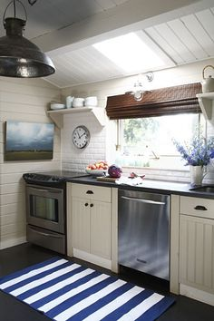 Bright and airy galley kitchen idea. I like the stainless steel with the wood and natural light. The painting, clock, brick and light fixture are also good accents.