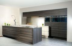 Een greeploze woonkeuken met laminaatdeuren en een doorlopend aluminium profiel. De horizontale houtstructuur, de rechte hoeken en de doordachte plaats van de keukentoestellen accentueren het strakke lijnenspel.