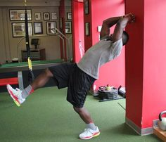 Total-Body Football Workout: Stand about 12 inches from a wall, facing away, with knees slightly bent. Extending your hips and spine, reach overhead with hands clasped into fists. Arch your back slightly and lean backward--lifting one leg out in front of you--to touch the wall. Try to control the movement as you slowly return to an upright position with both feet on the ground. Complete 10 to 15 reps, alternating legs. #SelfMagazine