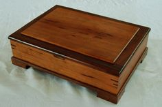 This cherry and walnut jewelry box at 13 x 9 1/2  x 4 has plenty of storage inside. The 12 compartments on the bottom are lined with burgundy felt and the removable sliding tray is divided into 3 sections. The lid has a raised center panel with a walnut frame and bridle joint corners for strength. I used an 8 continuous hinge that stays open when lifted up. The corners of the box have dbl. miter keys made of walnut. The entire box is sprayed with 3 coats of a furniture grade lacquer finish