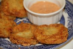 Fried green tomatoes dipped in milk, then dredged in a combination of flour, cornmeal and crumbled saltine crackers, then pan fried.  Frie...