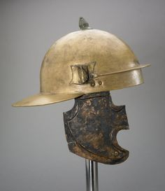 Copper alloy Roman legionary helmet, coolus type E. Hemispherical skull-cap, broad neck-guard, separate brow-guard attached by a rivet at either side and originally secured to the skull cap in front with solder. Tubular plume-holder and attachment for cheek-piece at each side, traces of knob on plume holder at top; hole for suspension in neck guard. Gash in front, repaired. Four punched inscriptions on neck guard.  J.M.VLVRI.-AVL- J.MAR--POSTVMVS I SER.RVFI J.MA.AVL.SAVPEI