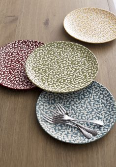 Bursting with lovely botanicals, these coupe-shaped accent plates mix and match with their counterparts in zinfandel, green, yellow and blue to set a colorful table or buffet. A wax-relief technique creates the design before the plate is dipped in colored glaze.