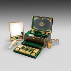 made 1850 by F West Manufacturer to the Royal Family This smart brass-bound ebony dressing case by F West is inlaid with a coronet above an intricate monogram and flush handles. It opens to reveal a green velvet interior with twelve cut glass vessels all with incised and chased silver gilt lids. The removable tray has a selection of ten various tools and the recess below is fitted with ivory brushes and a leather compartment containing a scent bottle, a horn-shaped posy holder, a key and a…