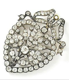 A late 19th century diamond brooch pendant. The openwork heart-shaped pendant, with flowerhead details, set with old brilliant-cut diamonds, to a rose and old brilliant-cut diamond bow surmount, mounted in silver and gold, circa 1880, 5.0 cm long, later brooch fitting.