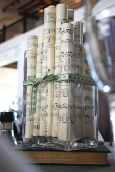 I want NON-floral centerpieces. LOVE this: rolled up sheet music. But Id add pearls around the outside and LARGE red bow/ribbon. - Click image to find more weddings posts