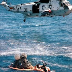 U.S. Navy Recovery helicopter hovers over the NASA  Apollo 16 Command Module while Navy divers work in the raft. Note the flotation collar around the base of the CM. Courtesy of the NASA Photograph Collection.