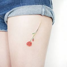 Red rose tattoo on the left thigh.