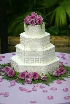 Torta multi-con gradas hermosa de la boda con helar blanco. La torta  se adorna con las rosas púrpuras. Foto de archivo