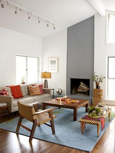 The homeowners kept the original architecture of the Idea Home. They use the open layout for a family-friendly space to play games and work on crafts. To emphasis the open floor plan, the homeowners painted all of the walls in the space the same pale shade of gray, then painted the fireplace a darker shade of gray to emphasis that feature and play up the high, vaulted ceilings.