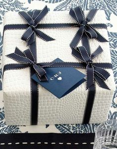 LOVE this look—white Christmas alligator gift wrap & black ribbons❣