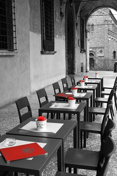 Outdoor Seating. Photography by Andrea Rea. In this juxtaposition of modern and historic, black tables are set with red placemats and menus outside a stylish Italian bar and restaurant in old city Bologna. Original work available as framed print, canvas and more only on Fine Art America and Pixels.com. https://andrea-rea.pixels.com/
