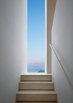 This clifftop holiday home by British designer John Pawson has rear large windows that face towards the sea