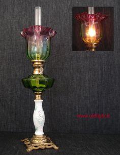 """Lampada  da tavolo Francese con  colonna in porcellana e base in bronzo dorato ; Serbatoio in cristallo verde con salva gocce brevettato; Bruciatore Wild & Wessel Kosmos 12"""";  Tubo in cristallo per  Kosmos 12'''; Paralume rarissimo tulipano  in cristallo verde con sfumatura cranberry."""