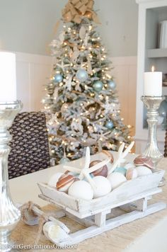 Coastal Christmas Tree with rope as garland, distressed wooden sea ornaments, blue netting ornament balls and a burlap bow as a tree topper. Gorgeous sleigh filled with coastal ornaments and starfish as a centerpiece Beach Christmas Trees, Coastal Christmas Decor, Nautical Christmas, Cottage Christmas, Christmas Tree Toppers, Christmas Home, Christmas Decorations, Christmas Crafts, Christmas Ideas