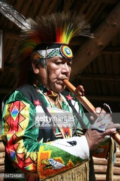 Stock Photo : Shuswap Cultural Guide Playing Indian Flute Inside Pit House At Historic Hat Creek Ranch's Native Village, British Columbia, Canada