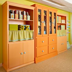 Wonder Wall: Basements often have large expanses of walls, which are perfect for wall units. This color-splashed storage unit instantly jazzes up the room. Open shelving keeps bright magazine holders and photo boxes visible, letting you see items at a glance. Grouping them by date or category makes organizing a cinch. Color-coordinated curtains bring a new level of interest to the piece while concealing contents that cannot fit below.