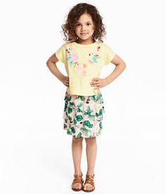 Hellgelb/Papagei. Set mit Shirt und Rock aus weichem Jersey. Kurzarmshirt mit Frontdruck. Rock mit asymmetrischen Volants und elastischem Bund.