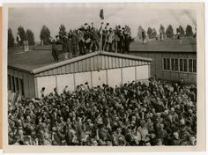 View of Dachau concentration camp prisoners cheering on their liberators. [Photograph #55315]  Date:	Monday, April 30, 1945  Locale:	Dachau, [Bavaria] Germany  Credit:	United States Holocaust Memorial Museum, courtesy of Joseph Eaton  Copyright:	United States Holocaust Memorial Museum