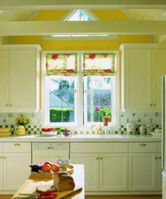 Stretch Above the Eaves    A small kitchen feels much bigger after a remodeling project reveals the slope of the roof. A triangular window adds to the brightness. Cabinets in basic white pair with yellow, green, and a touch of red for a lively cottage-inspired color scheme.