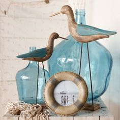 coastal style decor - blue bottles, wading birds, and life preserver frame (you could DIY the frame starting with a round frame and painting it like that)