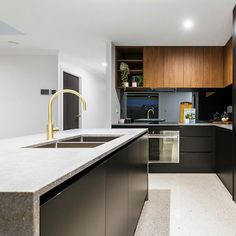 @lavish_constructions & @weston_kitchens super sleek Toowoomba Sienna House featuring Caesarstone Rugged Concrete across the Kitchen Bathroom & Laundry | Contrasting cabinetry in Matte Black against @polytec Florentine Walnut Woodmatt ____ Appliances by @boschaustralia @ariston_appliances @husky_refrigerators  Tapware by @phoenixtapware  Caesarstone joinery by @signaturestoneqld  ____ #caesarstone #caesarstoneau #ruggedconcrete
