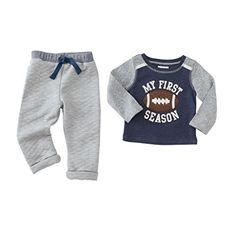 """Mud Pie Baby Boy Sport Star Football Pants & Shirt Set: Navy cotton ribbed top features contrast sleeves and neckline binding, twill tape shoulder accents, quilted football applique with twill tape and brass grommeted lacing, frayed natural canvas accents and layered brushed twill """"MY FIRST SEASON"""" sentiment with stitching detail. Pairs with heathered gray quilted jacquard pants featuring contrast ribbed waistband with twill tape drawstring and cuffed ankle openings."""