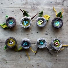 """Wee wool nest brooches, needled with care, speak to your optimism and love of nature.Each nest measures about 1.25"""" to 1.5"""" across and are surrounded with wool leaves which adds size and dimension to the brooch.  Stone or glass bead eggs are snuggled inside each nest. A pinback is sewn to the back."""
