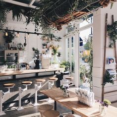 White walls, tons of plants and beautiful wood in this coffee shop.