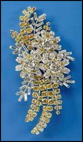 "Queen Elizabeth's ""Australian wattle brooch"". The Australian Wattle Brooch takes a floral approach to flying the Australian flag. Yellow diamonds depict sprays of wattle, the national flower. The wattle gives the brooch its name, but there's more flowery goodness going on: diamonds with a slightly blue color signify mimosa leaves, forming a background for diamond tea tree blossoms (each with a single large white diamond in the center)."