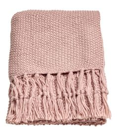 Dusky pink. Throw in soft, moss-knit fabric with wool content. Fringe at short sides.