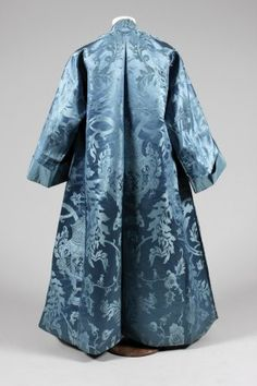 Banyan, circa 1730-40, of blue Chinese damask, woven with large-scale repeats of Chinese censors on stands, amid acanthus scrolls and exotic fruits, of simple kimono-like construction, lined in blue taffeta, with fold-back cuffs, no fastenings