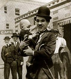 Charlie Chaplin on set with a baby - c.1915 (Isn't he sweet? Baby too, of course. c;)
