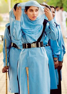 A policewoman, armed with a stick, fixes her veil while monitoring a rally in Islamabad, Pakistan. Photographer: Romeo Gacad