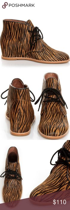"""Matiko Sharon Zebra Pony Hair Wedge Sneaker There will be no sharing the """"Sharon"""", because you'll want the Matiko Sharon Zebra Pony Fur Lace-Up Wedge Sneakers all to yourself! Get on-board with the wedge sneaker trend in the coolest tan and black tiger print pony hair, with a round toe and a lace-up panel with black shoestrings to match the black grommets and black leather trim. Beige top-stitching along sole. 2"""" hidden wedge heel. Cushioned insole. Non-skid rubber sole. Leather upper and…"""