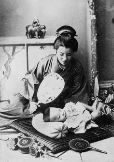 A Japanese mother fans her baby who is lying on a cushion on the floor. 1930, Japan.