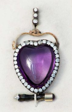 A Transforming Broach / Pendant  Decorated with a heart shaped amethyst (approx. 35 cts.), encircled with diamonds (approx. 3.5 cts.) mounted on gold and silver. Original box with small screwdriver decorated with an amethyst cabochon. 15.89 grams.