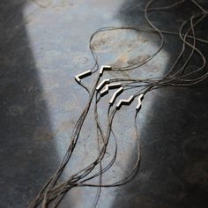 handmade of 925 silver on a string of vintage linnen twine seven variations one of a kind