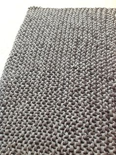 Hand knit rug. It is made with recycled tshirt yarn. This yarn is from Brazil and is a waste product from textile industry.