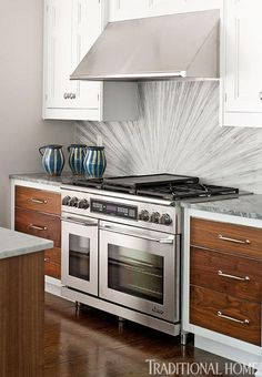 """Kitchen by Bob Bakes  The elaborate custom-designed backsplash becomes the centerpiece of the otherwise uncomplicated space—playing off the gray and white of the marble and drawing the eye to its intricate sunburst pattern.  """"I'm a big fan of accents and pleasant distractions in a room—whether through the subtle injection of color or shape or the drama of something like a custom-designed backsplash. Design should be fun and energetic."""""""