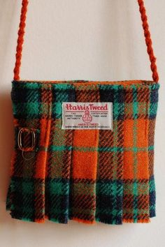 Small green and orange tartan Harris Tweed fashion accessory shoulder bags in the shape of a kilt, handmade on Orkney