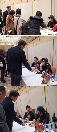 ノーマン・リーダスのブースにやってきたミーシャ・コリンズ(上)、握手を交わす2人(中)、ミーシャのためにサインするノーマン(下)