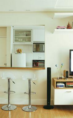 Com 36 m², este apartamento precisa de espaço. A sensação de amplitude é gerada pela integração dos ambientes, feita pela bancada. Revestida com uma lâmina de madeira, ela recebe uma placa de vidro, que é fácil de limpar. A transparência segue na decoração com as banquetas de acrílico.