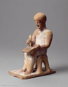 Homme assis écrivant | Musée du Louvre | Paris Scribe  Vers 525 - 475 avant J.-C.  Provenance : Thèbes  H. : 10,70 cm. ; l. : 7,50 cm. ; L. : 4,50 cm.  Acquisition, 1896